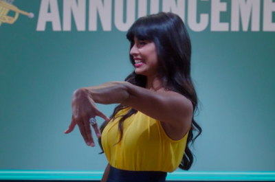 "Tahani showing off an enormous engagement ring. She's wearing a yellow sleeveless top and is in front of the superboard, which says ""ANNOUNCEME"" (the NT got cut off)"