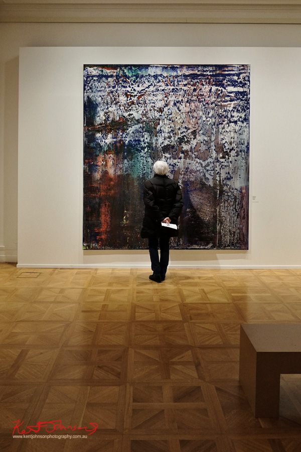 White haired gallery patron in a black parka looking at an abstract paining. Street Fashion Prague, Richter show at the Prague National Gallery, Kinsky Palace.