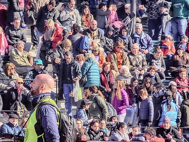 Gente en la tribuna con sol de frente
