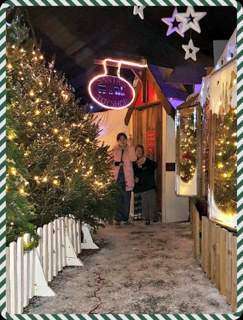 Three children with their magic golden keys about to enter Santa's toyshop
