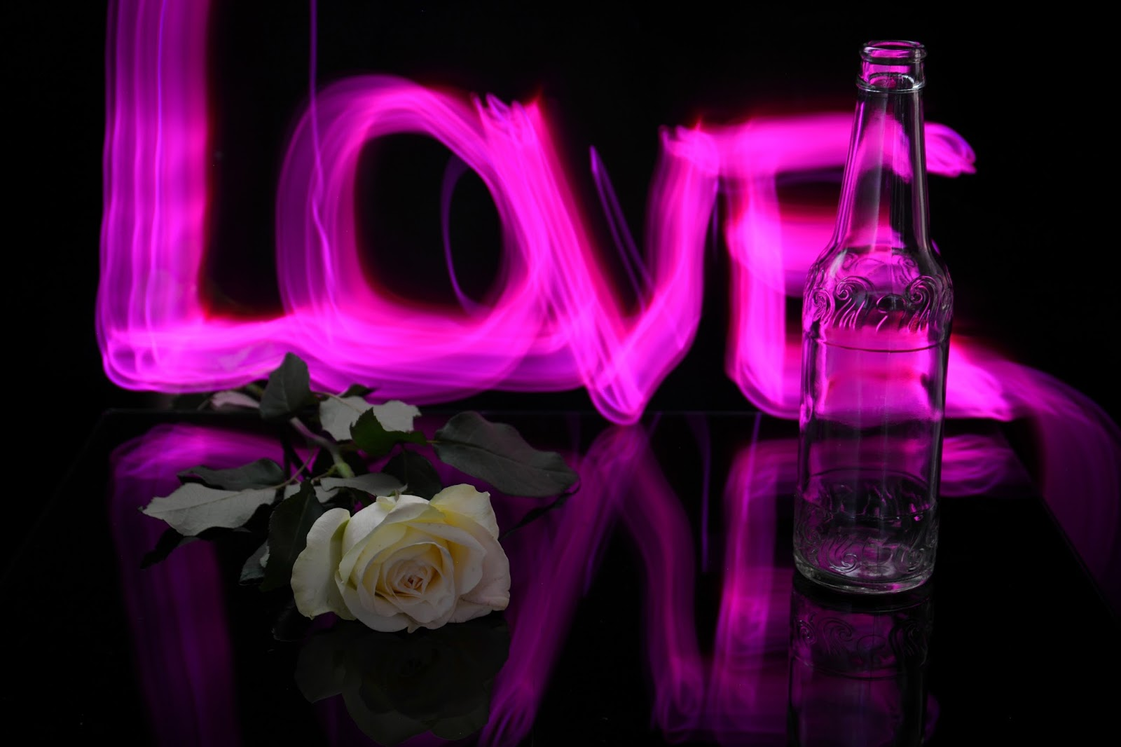 "painting with light ""Love"" in the background of a rose and a bottle on a mirror"