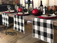 A table set with black and white plaid clothes and red ornaments and plates