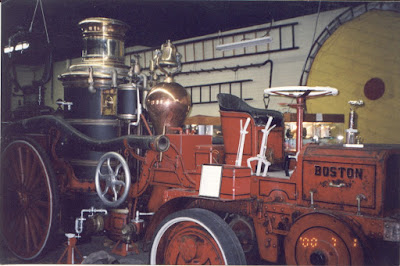 A red fire truck that would have been pulled by a horse. In the back there is a large black metal tank and a smaller, bulb-shaped tank that has the gleam of copper
