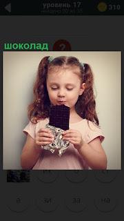 В руках у маленькой девочки большая плитка шоколада, которую она ест