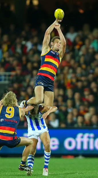 Brodie Smith of the Crows flies over Andrew Swallow of the Kangaroos to take a mark.