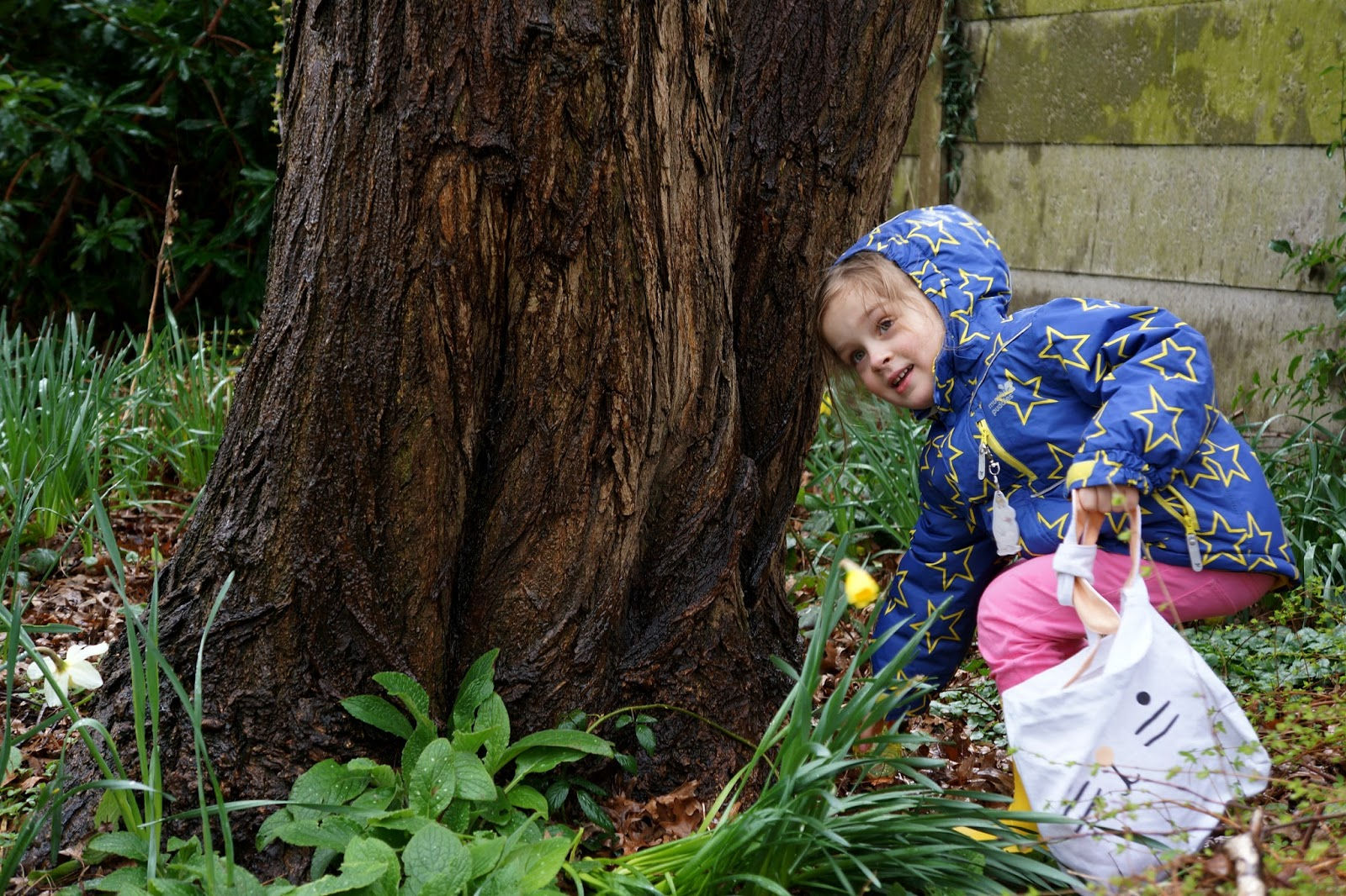 Little girl picking up an Easter egg under a tree