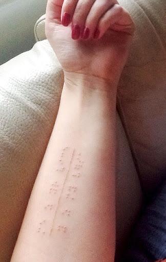 O branco da tinta da tatuagem sente em Braille