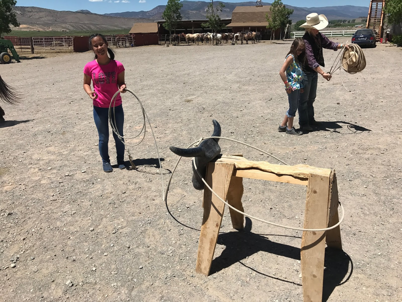 Female student has roped a practice bull with her lasso while another student gets up close to a lasso with a staff member.
