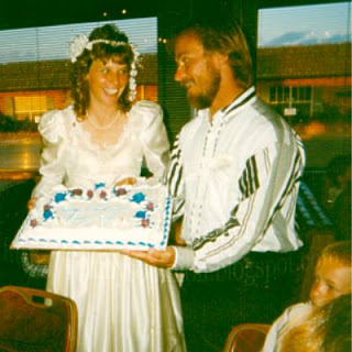 Cindy and Jimmy holding wedding cake during reception surrounded by children