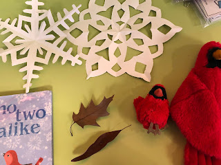 two paper snowflakes, No Two Alike book, two brown leaves, two red bird puppets