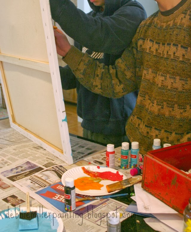 teenagers collaborating on a painting