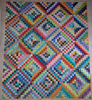 Scrappy Trip Around the World quilt with red, orange, and yellow on the main diagonal