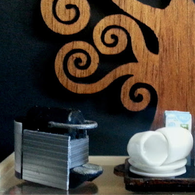 Modern miniature credenza in front of a black wall with a large wooden tree of life on it. On the credenza is a Nespresso machine and a tray with cups, saucers, milk.