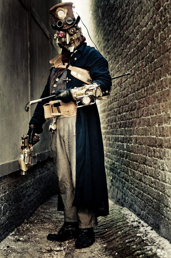 Man in a steampunk costume with a metal mask, goggles, top hat, gun, cane. Men's masked steampunk cosplay and fashion.