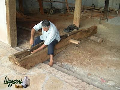 Bizzarri ajudando a terminar o cocho de madeira no monjolo de madeira Jacarandá. No meio da peça do monjolo o eixo de madeira que vai fazer o monjolo funcionar.