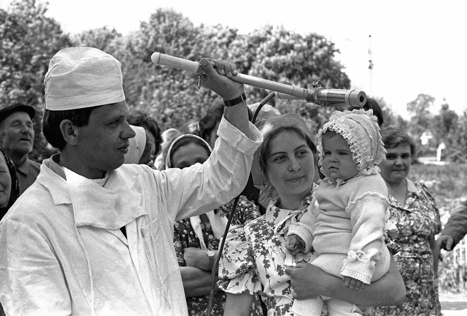 A Soviet technician checks the toddler Katya Litvinova during a radiation inspection of residents in the village of Kopylovo, near Kiev, on May 9, 1986.