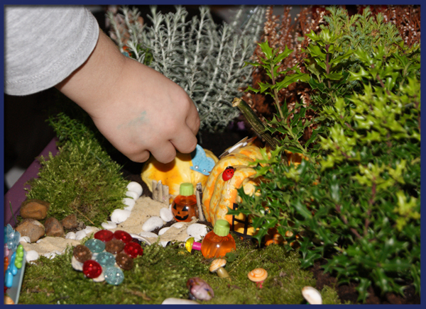 With the grass in place it just needs the finishing touches of the mushrooms that we made earlier to be placed on the land, we found various button shapes such as snails and watercans we made for ideal ornaments too, and this is the part I feel is perfect for your children to do as they really will decorate in the system a fairy would.  At least that's how I image it to be, unless like me, there are some neat freak fairies around....