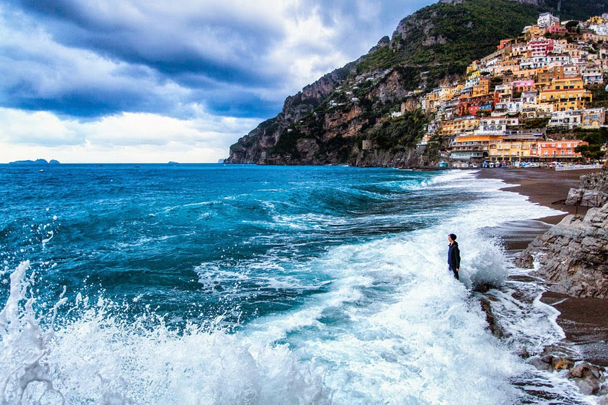 Everything about this image from Positano, Italy is captivating. From the colored houses dotting the steep hillsides, to the crystal clear water lapping up on shore. In fact the natural sights are so gorgeous you almost forget to notice the woman being splashed by the waves is fully dressed, cap and all. - Tiny Humans Lost In The Majesty Of Nature
