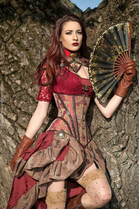 Woman wearing red steampunk clothing. Maroon lace blouse, burgundy brocade underbust corset with matching skirt, brown gloves, pocket watch, necklaces, collar and folding fan.