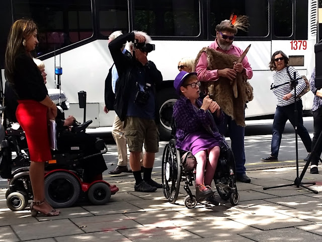 Kelly Vincent is in a purple outfit, sitting in her wheelchair making a speech with the microphone in her hands. To her left is the MC Joanne Blesing in a motorised wheelchair with her assistant who is wearing a red skirt and black top. Behind Kelly is a senior Aboriginal Man wearing a pelt over a pink shirt and jeans. He has a hat with black and red feathers. He is holding a message stick. Around these people are a photographer, and a pedestrian walking by behind them with a white top with fine black stripes and jeans.