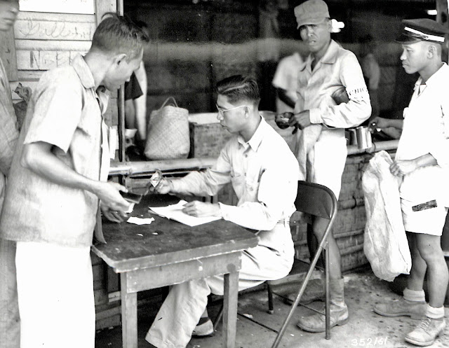 PCAU in operation, Filipino is making a purchase at the counter.  Taken 15 April 1945.