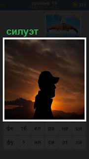 на фоне заката виден силуэт человека в кепке