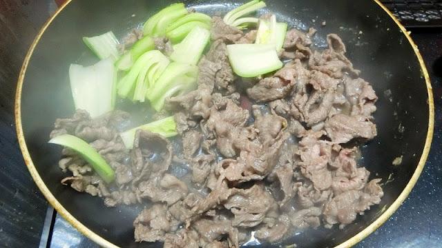 牛肉にチンゲンサイの茎を加えて炒め合わせる