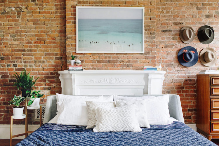 naked brick wall bedroom, ikea planter, white fireplace, interior design
