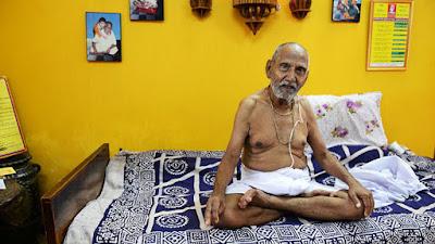 monje hindú de 120 años sentado en la cama