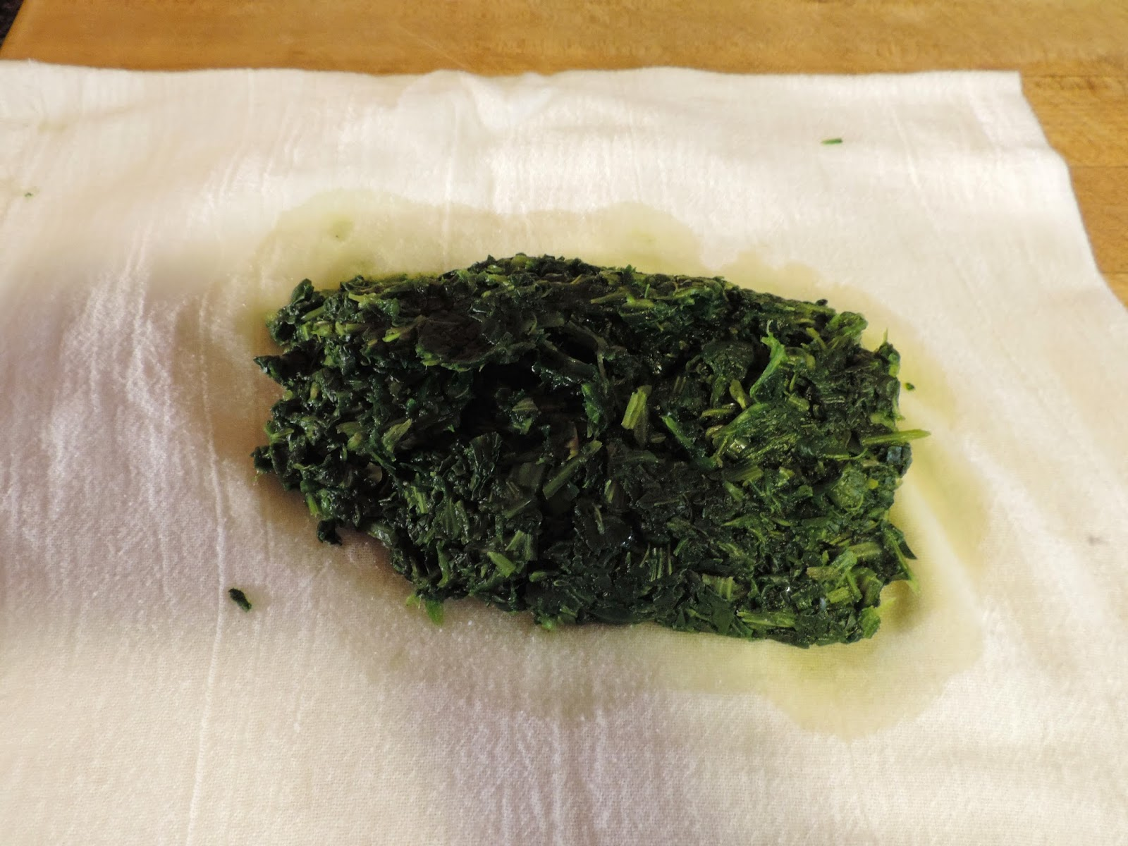 The spinach wrung dry in a towel.