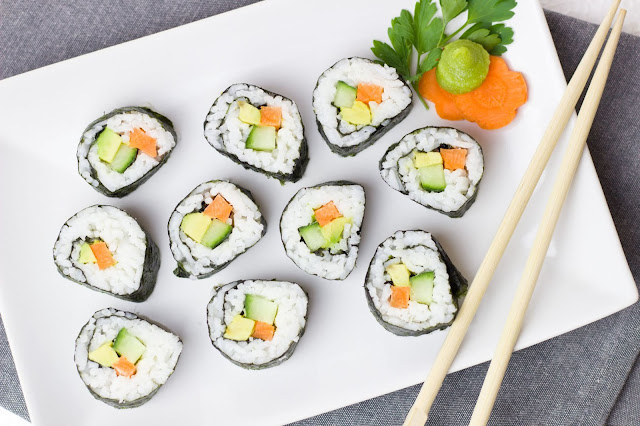 Sushi rolls on white square plate with chop sticks