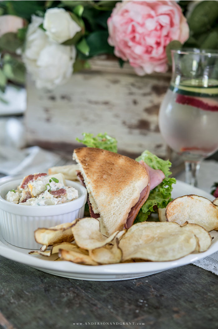 Plate with sandwich, potato salad, and potato chips.