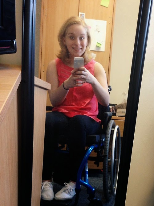 "Young woman with blonde hair, smiling, sitting in a blue manual wheelchair, taking a ""selfie"""