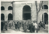 A black and white photograph of a crowd standing outside Memorial Field.