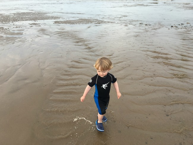 An-Indian-Summer-toddler-in-wetsuit-on-beach-at-Ogmore