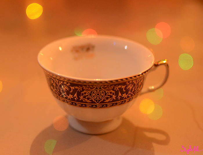 Image of a gold decorated teacup on a marble surface surrounded by bokeh light effects