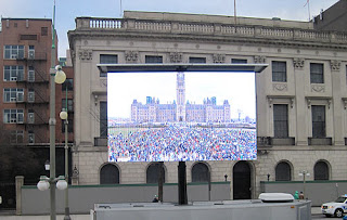 Screen showing the crowds on Parliament Hill.