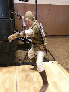 Someone in a Link costume, in a battle pose with a sword