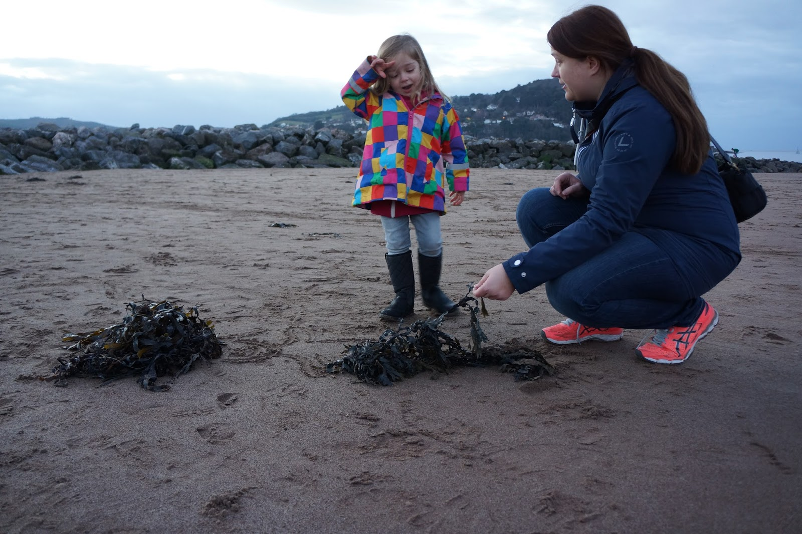 mum and daughter playing with seaweed on beach at butlins minehead
