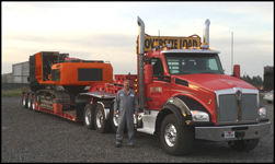 Greg Pellham stands with one of his Kenworth T880s