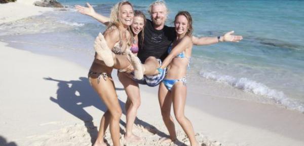 Richard Branson en la playa rodeado de mujeres