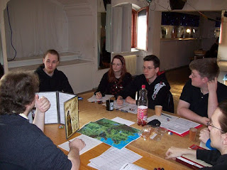 A group of players sitting around a table covered with books and dice playing a game of Dungeons and Dragons.