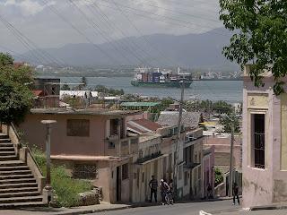 Kuba, Santiago de Cuba, die Bahía de Santiago de Cuba, Blick über abwärts zum Hafen führende Gassen, ein riesiges Containerschiff läuft ein.