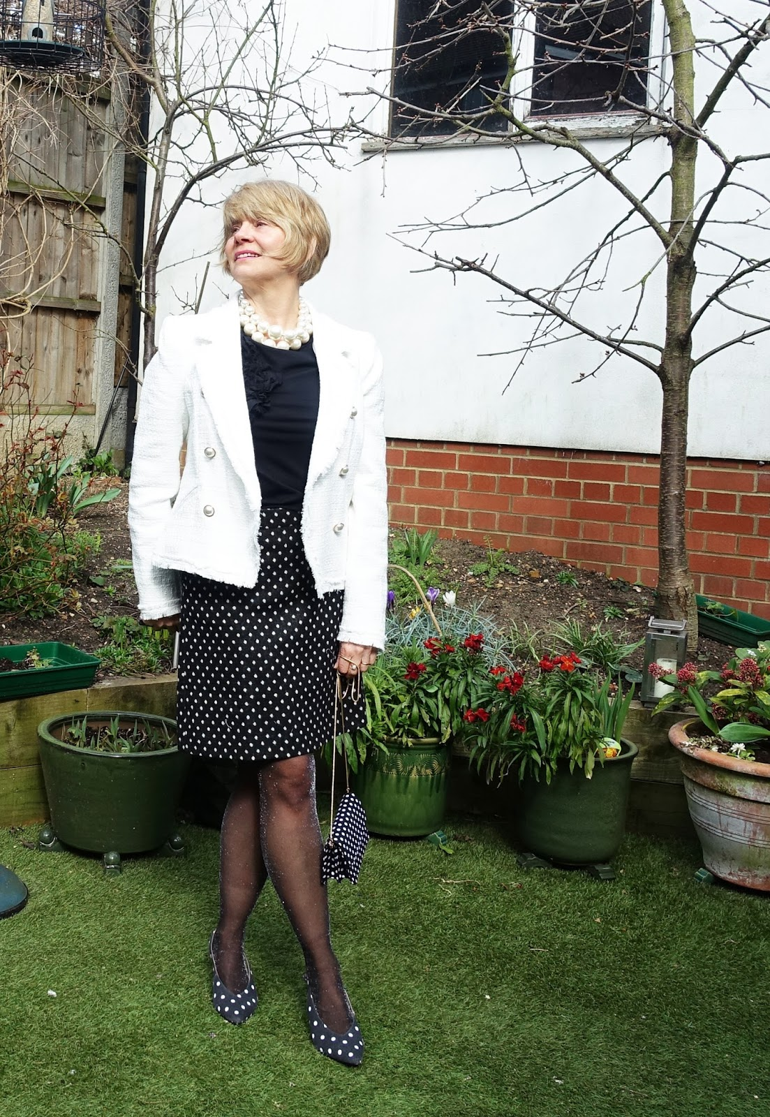 Image showing over 45s blogger Is This Mutton? wearing a white bouclé jacket worn with pearls and polka dots