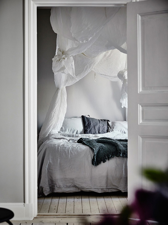 Grey bedroom and bed with drapes via Entrance Maklery