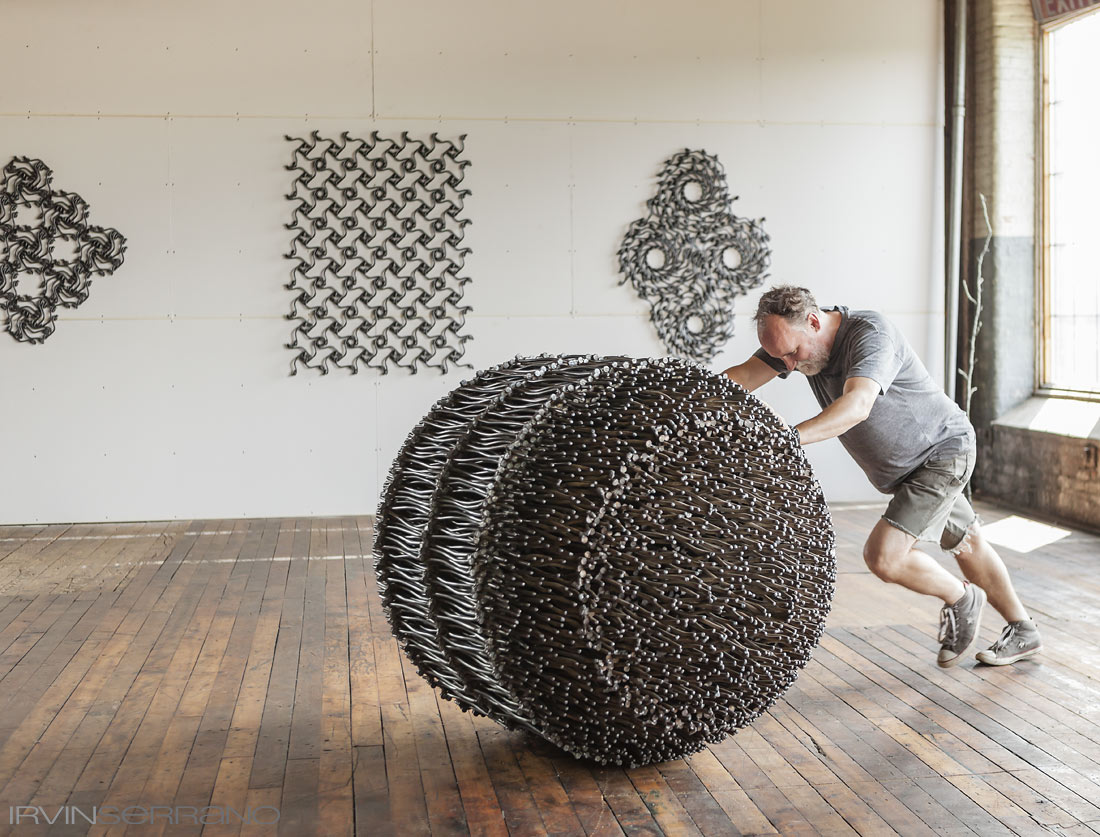 Artist John Bisbee rolls one of his sculptures made from nails across his studio in Brunswick, Maine.