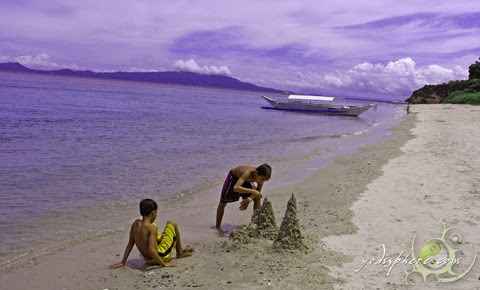 Two children building sand castles at the beach.