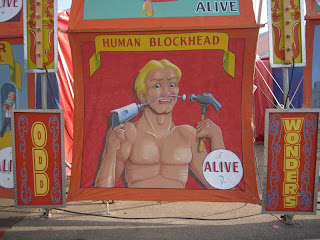 Blockhead painted sign with man drilling screws into his face