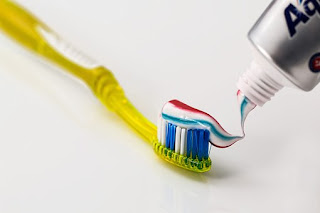 a toothbrush with a toothpaste on top