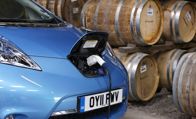 Nissan Leaf charging next to Scotch whisky barrels